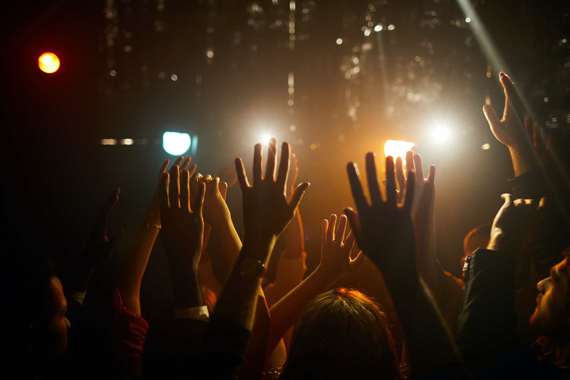 People waving hands at concert